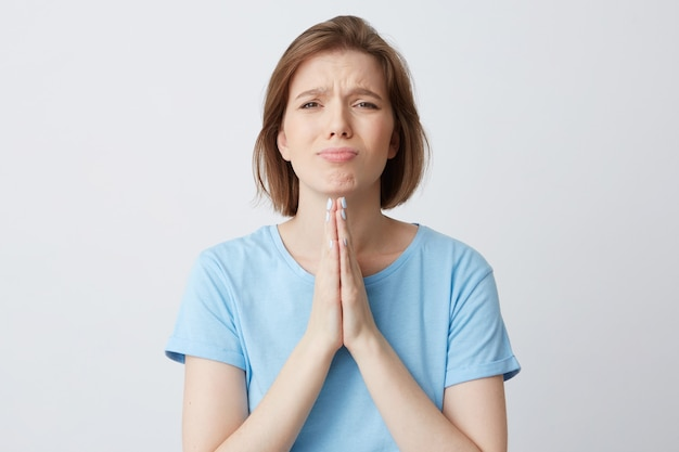Portrait of sad desperate young woman in blue t shirt keeps hands in praying position
