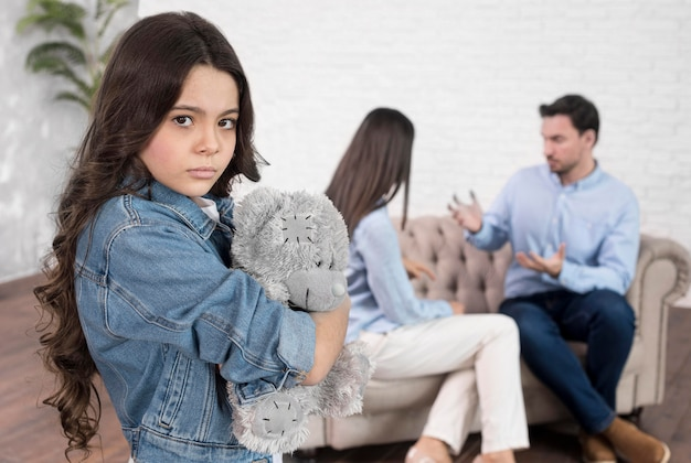 Portrait of sad girl holding teddy bear