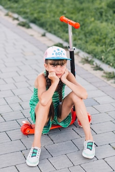 Portrait of a sad girl wearing cap sitting on red push scooter