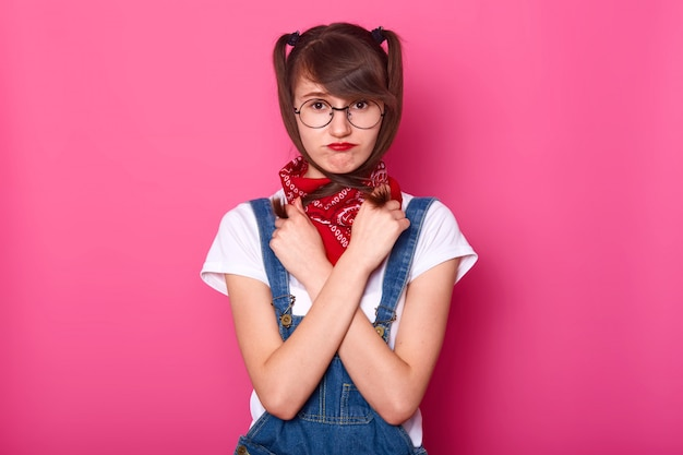 Portrait of sad girl wears white t shirt, denim overalls, with bandana on neck. schoolgirl crossed hands on chest, holds pigtails, looks upset, does not want to come back to school after holiday.