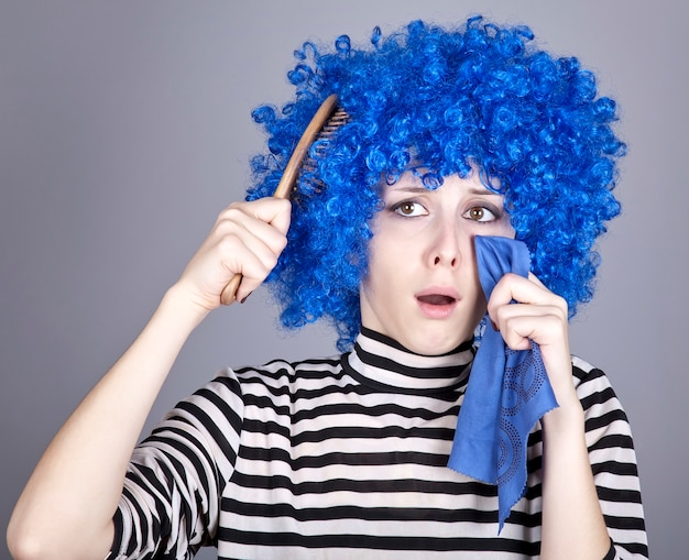 Portrait of sad girl with blue hair and comb.
