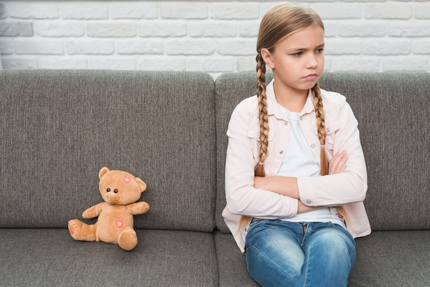 Portrait of a sad girl with crossed arms sitting near the teddy bear on gray sofa