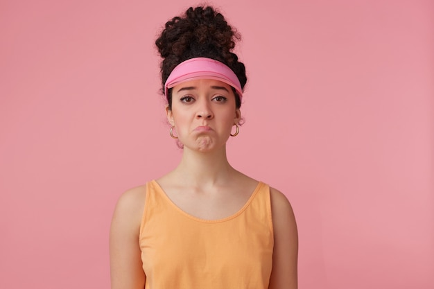 Portrait of sad girl with dark curly hair bun. wearing pink visor, earrings and orange tank top. has make up. emotion concept. pouts a lip
