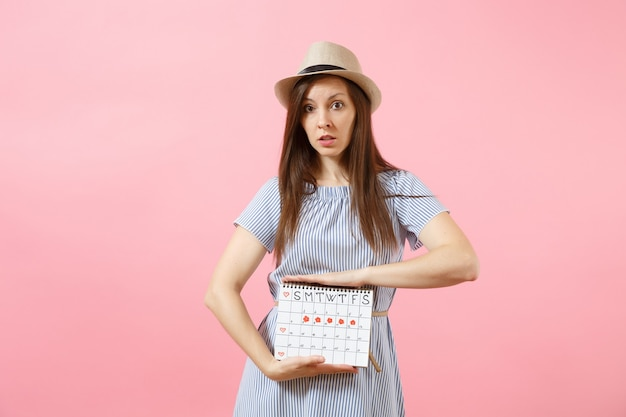 Portrait sad illness woman in blue dress holding periods calendar for checking menstruation days put hand on abdomen isolated on pink background. medical, healthcare, gynecological concept. copy space