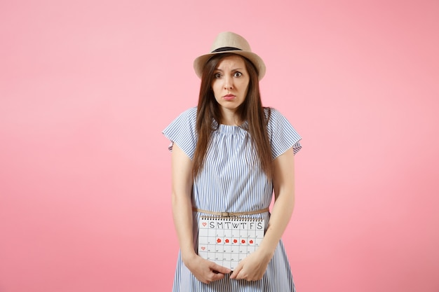 월경일을 확인하기 위한 기간 달력을 들고 있는 파란 드레스를 입은 슬픈 질병 여성은 분홍색 배경에 격리된 복부에 손을 얹었습니다. 의료, 건강 관리, 부인과 개념입니다. 복사 공간