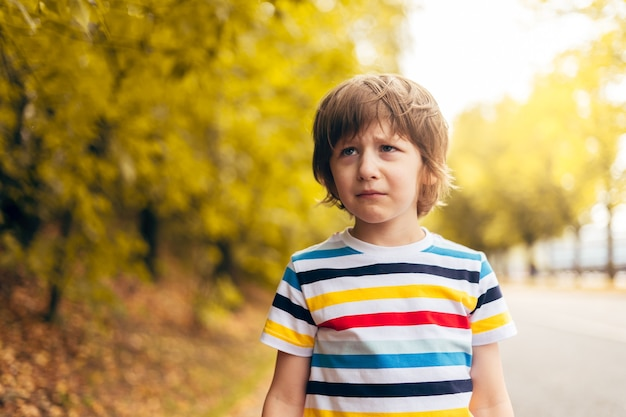 Portrait of sad little child in the autumn on the nature walk outdoors
