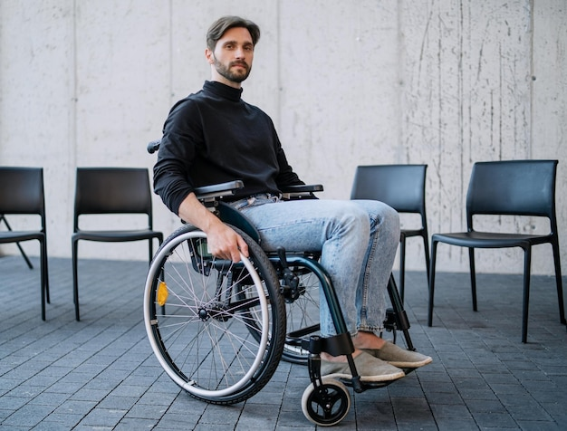 A portrait of sad man in wheelchair on group therapy, looking at camera.
