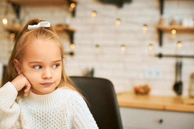 Portrait of sad moody seven year old female child in cozy warm sweater spending cold winter day at home alone, keeping hand under her chin, having thoughtful upset facial expression, looking away