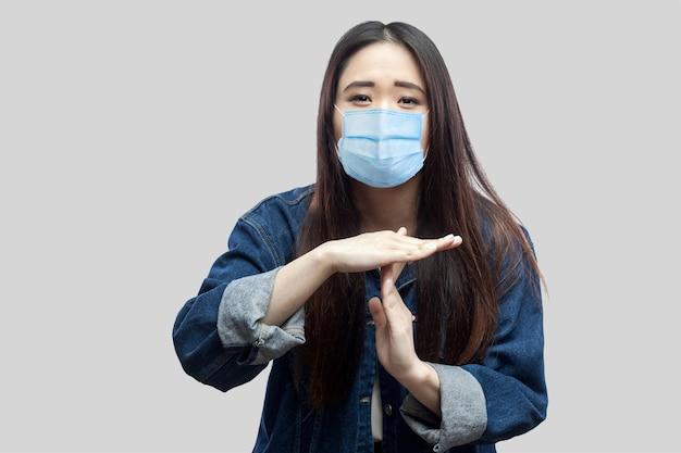 カジュアルな青いデニムジャケットの外科医療マスクと立って、タイムアウト記号でカメラを見ているブルネットのアジアの若い女性の悲しい肖像画。灰色の背景に分離された屋内スタジオショット。
