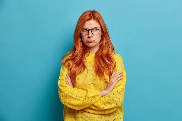 Ritratto di donna rossa offesa triste piega le braccia e porta le labbra tristi dopo la rottura o litigare con il fidanzato reagisce alle parole negative ha un'espressione del viso sconvolta vestita di maglione giallo.