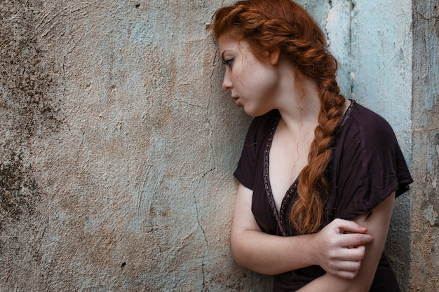 Portrait of a sad red-haired girl, sadness and melancholy in her eyes