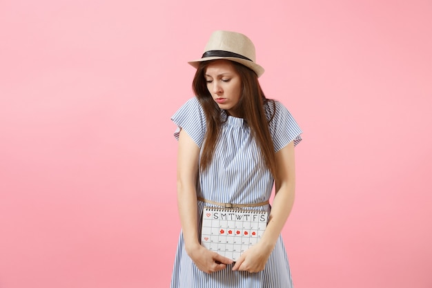 Portrait sad sickness woman in blue dress holding periods calendar for checking menstruation days put hand on tummy isolated on pink background. medical, healthcare, gynecological concept. copy space.