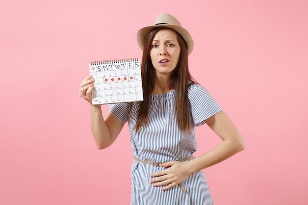 월경일을 확인하기 위한 기간 달력을 들고 있는 파란 드레스를 입은 슬픈 질병 여성은 분홍색 배경에 격리된 배에 손을 얹었습니다. 의료, 건강 관리, 부인과 개념입니다. 공간을 복사합니다.