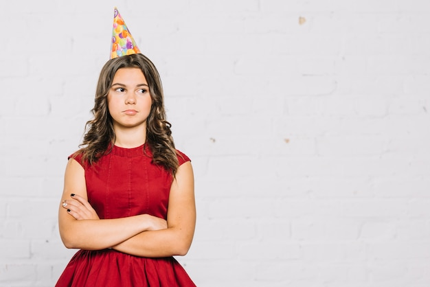 Portrait of sad teenage girl wearing party hat standing with her crossed arms