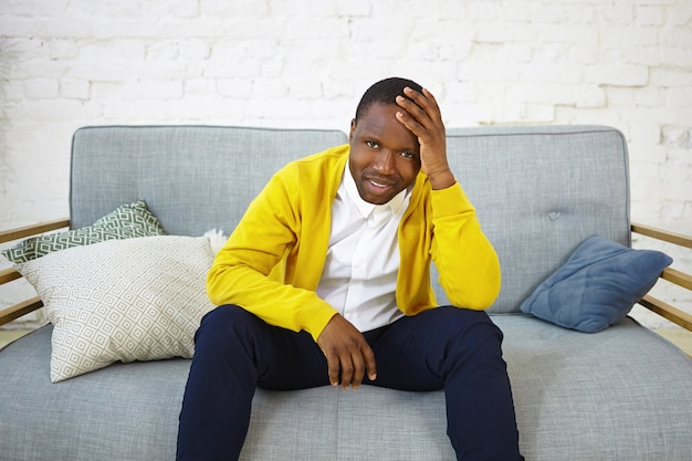 Portrait of sad unhappy african male in yellow cardigan sitting on couch with decorative pillows, keeping hand on head, feeling nervous while watching tv football match, having worried expression