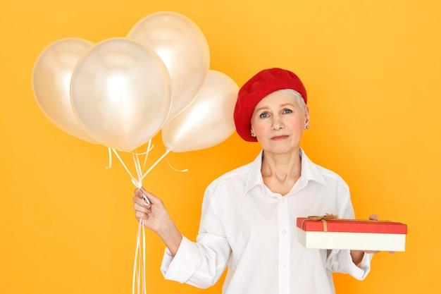 Ritratto di triste infelice donna matura in abiti eleganti in posa agaisnt sfondo giallo con scatola di cioccolata ed elio palloncini, dando regalo di compleanno, avendo sconvolto espressione depressa