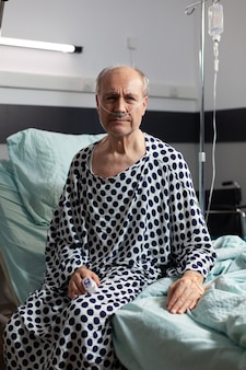 Portrait of sad, unwell senior man sitting on the edge of hospital bed with iv drip attached and breathing with help from oxygen mask, looking at front