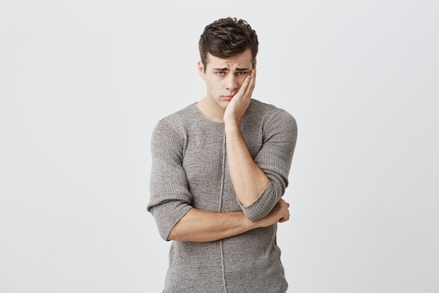 Portrait of sad upset young blue eyed male with dark hair, wearing sweater, keeping hand on cheek, frowning his face, looking with sad expression , because of bad news he received.