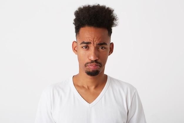 Il ritratto del giovane sconvolto triste con i capelli ricci indossa la maglietta sembra labbra depresse e ricurve isolate sopra il muro bianco