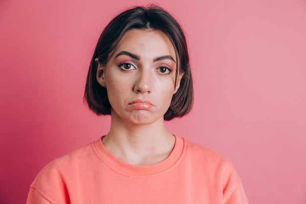 Portrait of sad upset young woman with bright makeup on pink background