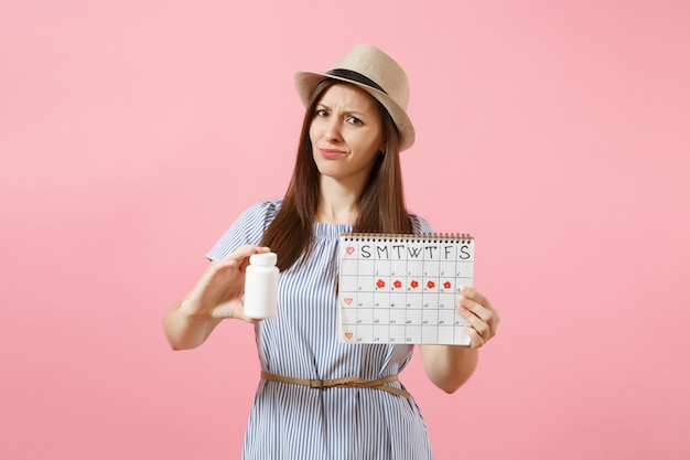 Portrait of sad woman in blue dress holding white bottle with pills, female periods calendar, checking menstruation days isolated on background. medical healthcare, gynecological concept. copy space.