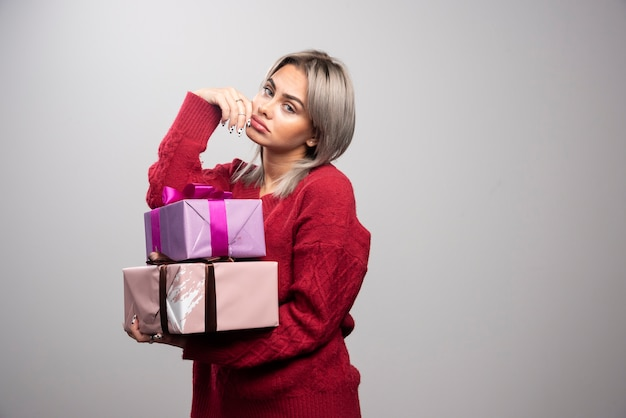 Portrait of sad woman holding gift boxes on gray background.