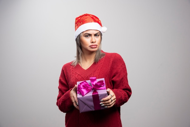 Portrait of sad woman posing with holiday gift on gray background.