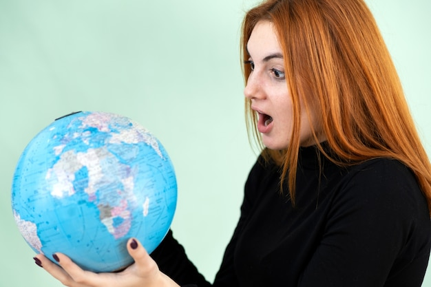 Portrait of a sad worried young woman holding geographic globe of the world in her hands. travel destination and planet protection concept.