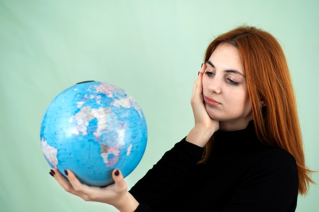 Portrait of a sad worried young woman holding geographic globe of the world in her hands