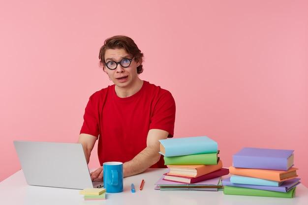 Ritratto di triste giovane studente con gli occhiali indossa in maglietta rossa, si siede al tavolo e lavora con il computer portatile, sembra infelice, isolato su sfondo rosa.