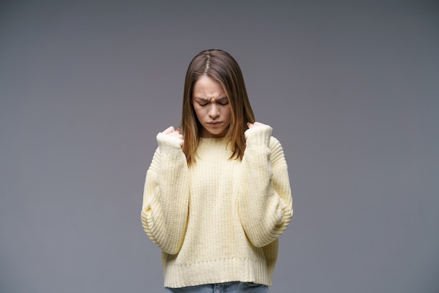 Portrait of a sad young woman of caucasian ethnicity clenches her fists in a yellow sweater on a gra...