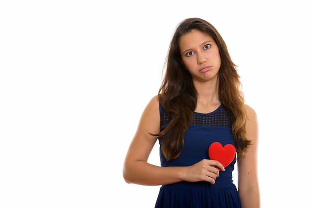 Portrait of sad young woman holding heart while looking upset