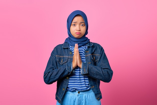 Portrait of sadness young asian woman showing praying gesture on pink background