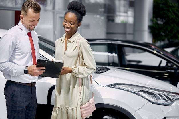 Portrait of salesman and african woman client having conversation in car showroom