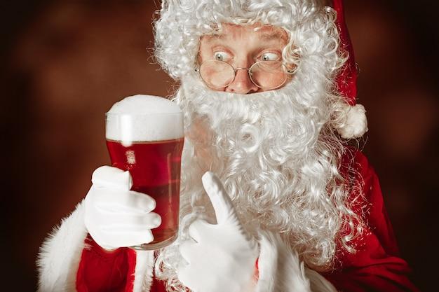 Ritratto di babbo natale in costume rosso con una birra
