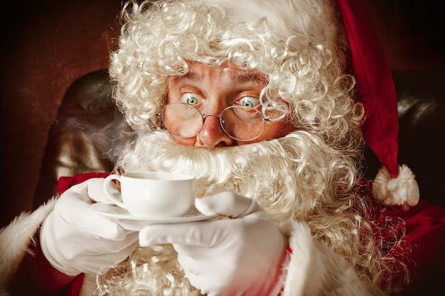 Ritratto di babbo natale in costume rosso con una tazza di caffè