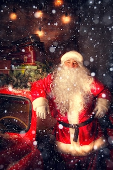 Portrait of santa claus. santa claus is standing near the car with gifts