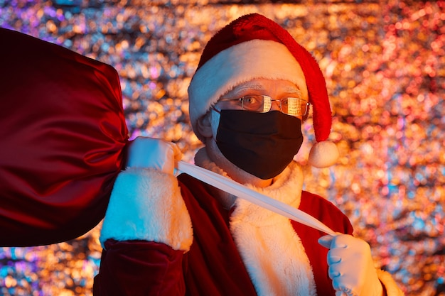 Portrait of santa claus wearing protective mask carrying bag of presents for holiday