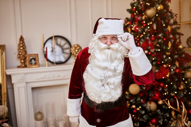 Portrait of santa claus with glasses near the fireplace and christmas tree with gifts.