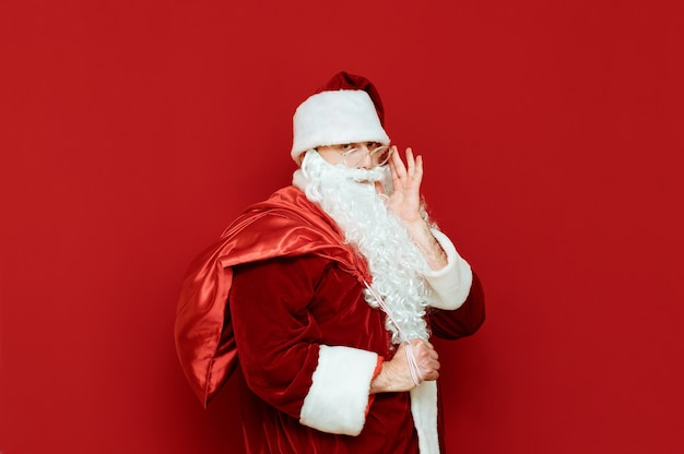 Portrait of santa claus with heavy bag with gifts
