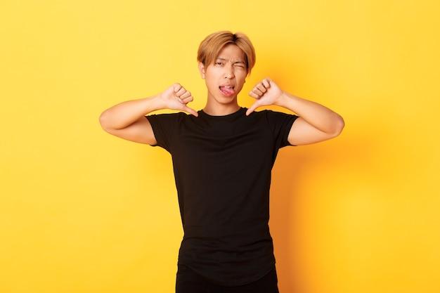 Ritratto del ragazzo bello asiatico impertinente che mostra il pollice in giù e la lingua del bastone delusa, giudica qualcosa di brutto, muro giallo