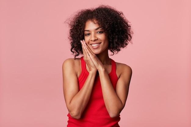 Portrait of satisfied african american woman with afro hairstyle feels pleasure, smiles, rejoices, folded hands as going to sleep, get compliments flirts, wearing red singlet, isolated on pink wall