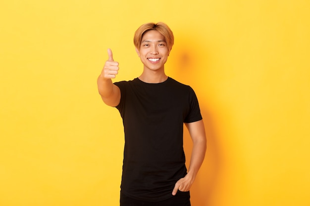 Portrait of satisfied asian man with blond hair, standing over yellow wall and showing thumbs-up