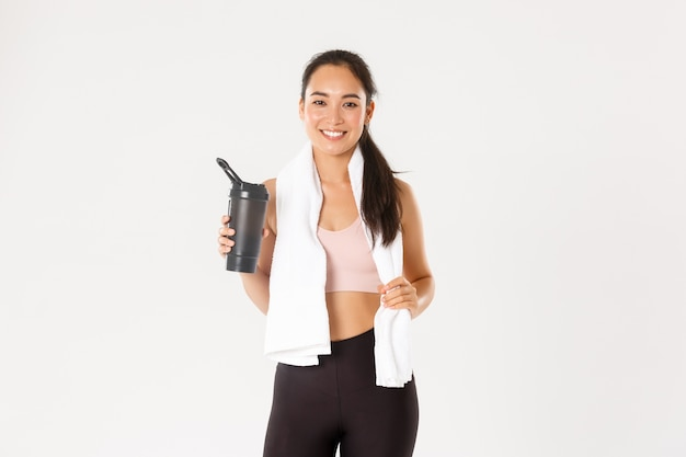 Portrait of satisfied attractive asian fitness girl with cute smile, looking pleased wiping sweat with towel and drinking water after workout.