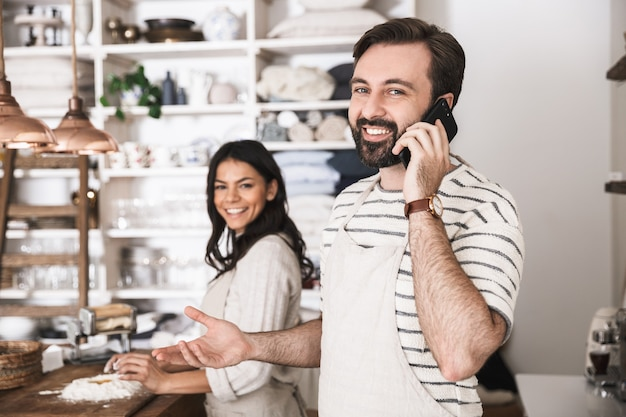 Portrait of satisfied couple man and woman 30s wearing aprons using smartphone while cooking together in kitchen at home