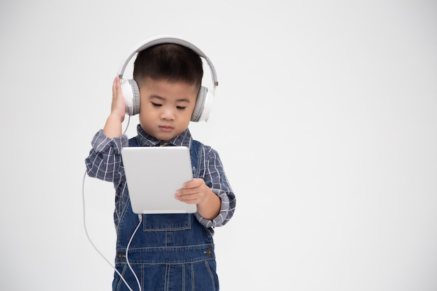 Portrait of a satisfied cute little kid holding tablet and listen music