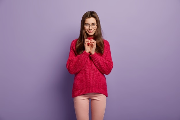 Portrait of satisfied european female keeps hands together, has intention to do something, wears red jumper and trousers, isolated over purple wall hmm, let me think, i have nice plan