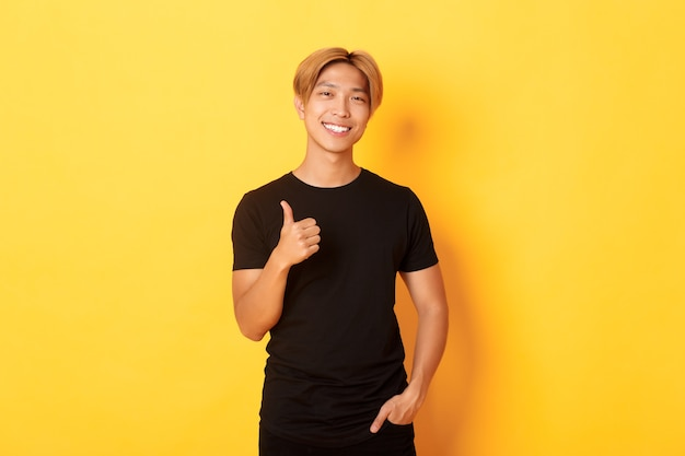 Portrait of satisfied handsome asian blond guy, smiling pleased, showing thumbs-up in approval, standing yellow wall