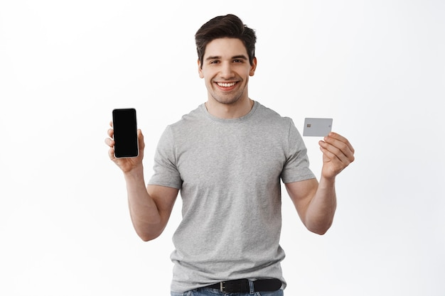 Portrait of satisfied handsome man showing empty smartphone screen and plastic credit card, demonstrate phone app, banking and finance concept