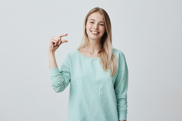 Portrait of satisfied happy caucasian female model with blonde smiling broadly demonstrating size of something